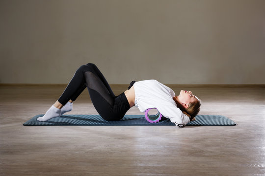 A beautiful slim young girl of European appearance demonstrates exercises with a gymnastic roller for yoga and relaxing her back.