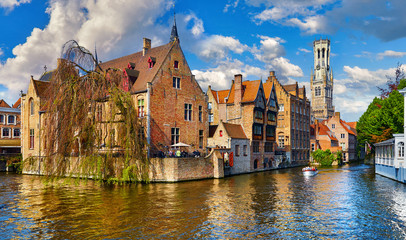 Fototapete - Bruges, Belgium. Ancient medieval european city. View at tower Belfort van Brugge and vintage building at bank of Rozenhoedkaai channel river. Panoramic view with blue sky and clouds. Famous tourist.