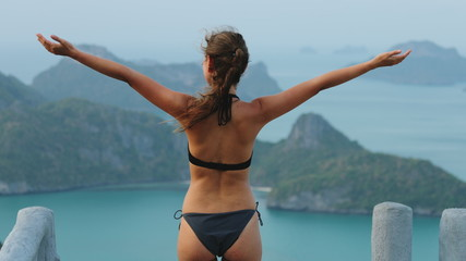 Young Woman Enjoy Ang Thong National Marine Park. Back View of Girl in Bikini Rising Hands Tropical Islands on Background. Female Traveler Contemplating Thailand Nature.