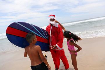 Carlos Bahia, dressed as Santa Claus, greets children at the Maresias beach in Sao Sebastiao