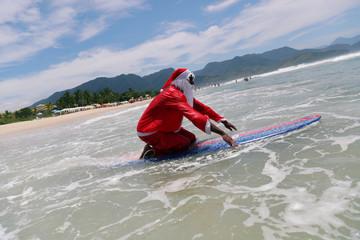 Carlos Bahia, dressed as Santa Claus, enters the sea to surf at the Maresias beach in Sao Sebastiao, hometown of WSL World Champion Gabriel Medina