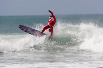 Carlos Bahia, dressed as Santa Claus, surfs at the Maresias beach in Sao Sebastiao, hometown of WSL World Champion Gabriel Medina