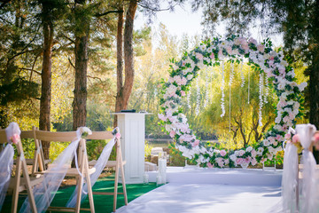 Wedding ceremony. Floral wedding decor in the park. American wedding. Chairs, arch and flowers for a wedding ceremony in a park