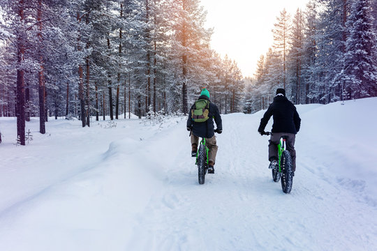two people with fat bikes riding snowy winter forest trail in finland