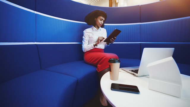 A successful charming African-American female is sitting on a bent sofa of classic blue color and using her digital tablet; laptop, smartphone, paper cup on the table, a copy space area on the left