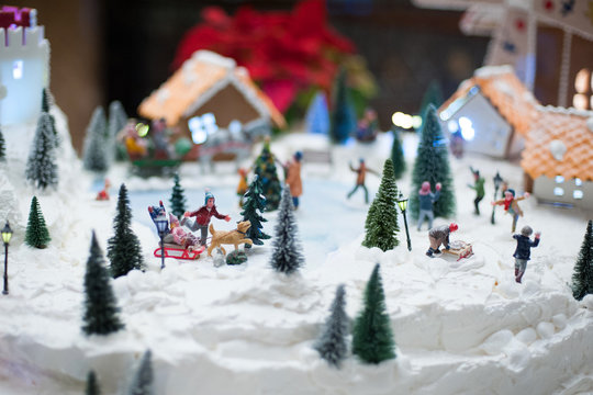 Little toy Christmas miniature with people skating and playing snowballs