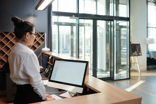 Young female receptionist standing in front of computer screen by counter