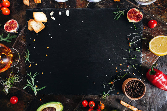 Cooking dark stone board with herbs, spices and vegetables. Top view with copy space