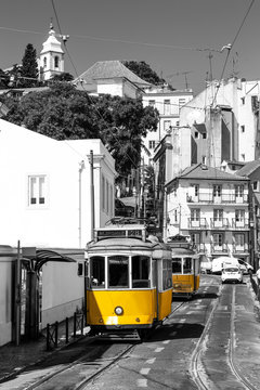 Yellow tram on old streets of Lisbon, Alfama, Portugal. Black and white picture with a coloured tram.