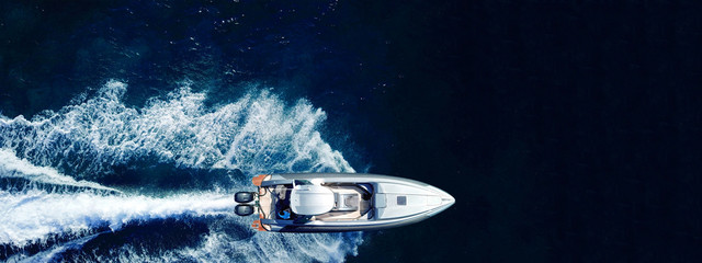 Aerial drone ultra wide top down photo of luxury rigid inflatable speed boat cruising in high speed...
