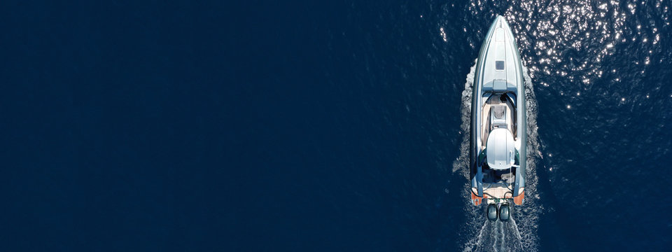 Aerial drone ultra wide top down photo of luxury rigid inflatable speed boat in Aegean deep blue sea, Greece
