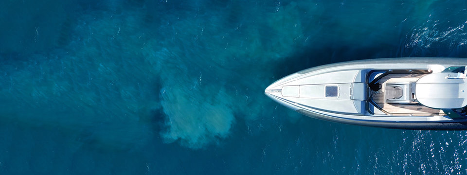 Aerial drone ultra wide top down photo of luxury rigid inflatable speed boat cruising in high speed in Aegean deep blue sea, Greece