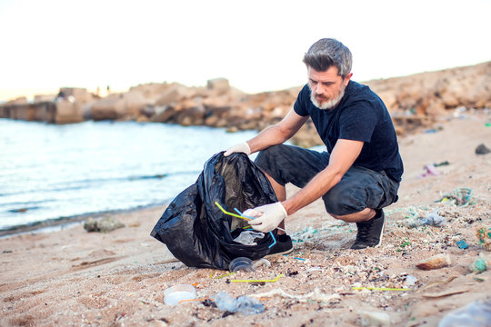 Man with white gloves and big black package collecting garbage on the beach. Environmental protection and planet pollution concept