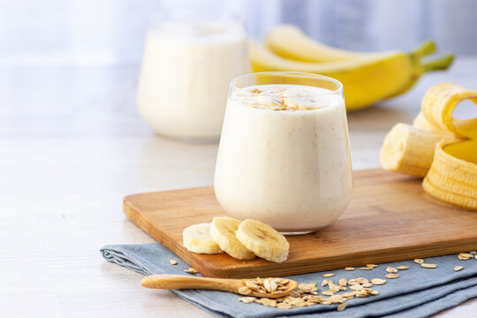 Vegan banana and oatmeal smoothie in glass jar on the light background. Healthy food.