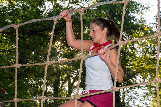 fit slim woman obstacle course race on rope ladder