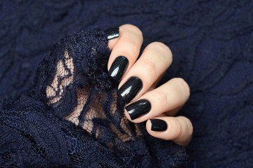 Door stickers Manicure dark blue manicure with a shimmer against a lace background
