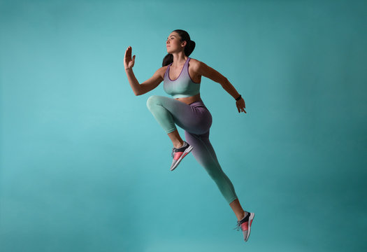 Athletic young woman running on turquoise background, side view