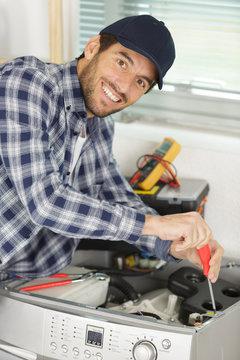 plumber installing water shutoff valve for washing machine at home