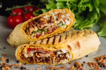 Spoed Fotobehang Snack Shawarma sandwich gyro fresh roll of lavash pita bread chicken beef shawarma falafel RecipeTin Eatsfilled with grilled meat, mushrooms, cheese. Traditional Middle Eastern snack. On wooden background