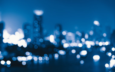 Bokeh background of skyscraper buildings in downtown. Urban city with lights, Blurry photo at night time.  illuminated Cityscape