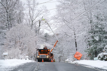 manual worker working on repair electrical line after winter snow storm