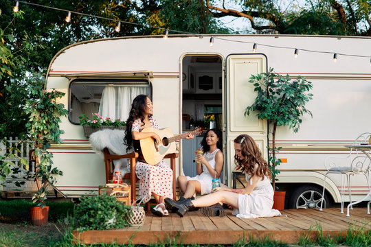 Laughing happy women with guitar have fun together outdoors near their camper van during summer travel