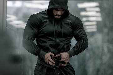 sport mind male motivation concept of epic movie hero strong bearded man in hoodie preparing for weight lifting during indoor gym workout training