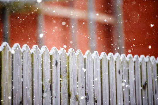 Wooden village fence in winter and snowfall