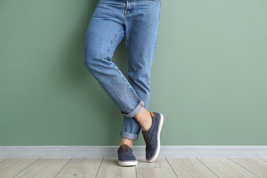 Young man in stylish shoes near color wall