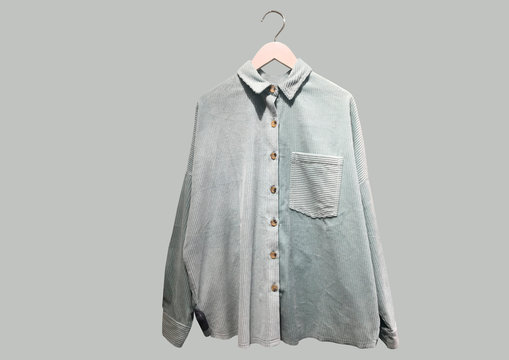 Light green casual corduroy shirt with pocket on a hanger isolated on gray background. Women's look. Flat lay. Minimal style. Composition of clothes. Pattern. Trendy clothes collage. Women's look