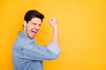 Photo of casual brown haired cheerful positive man overjoyed near empty space demonstrating muscles isolated vivid color background Wall mural