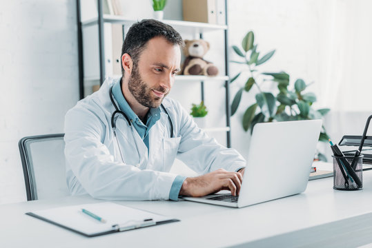 positive doctor sitting at workplace and using laptop