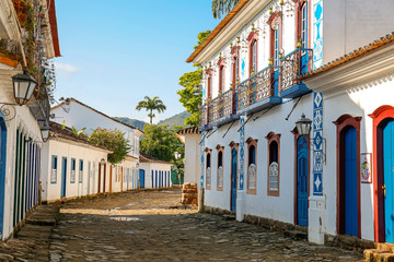 View to a cobblestone street with artful decorated house facades in historic town Paraty, Brazil