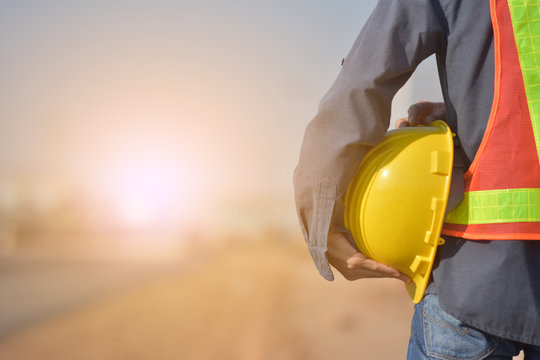 Close up Engineering holding Yellow helmet hard hat safety and Road construction background