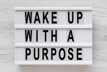 'Wake up with a purpose' words on a modern board on a white wooden background, top view. Overhead, from above, flat lay. Close-up.