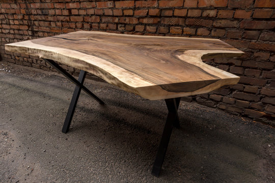 Wooden stylish table made of solid walnut with epoxy resin on the background of a brick wall