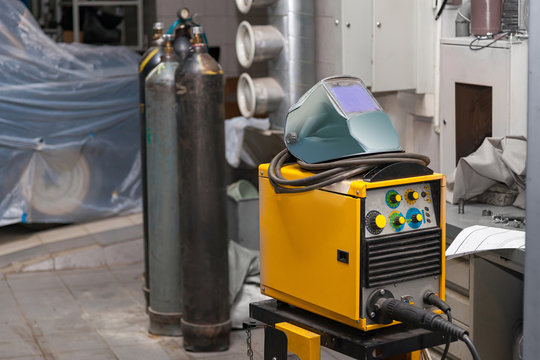 A yellow welding machine with a protective mask on top stands in a metal workshop near carbon dioxide cylinders. Industry and production. Construction works.