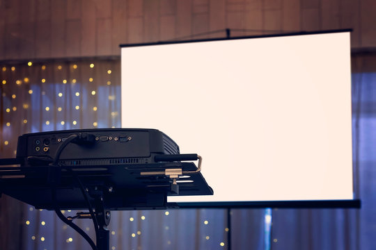 A view to the projection screen equipment at the decorated window curtain background of a banquet hall. Facilities for video and audio projection at a festive event. Show arrangement at a banquet.