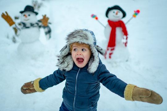 Winter portrait of little boy child in snow Garden make snowman. Child playing with Snowman on snow background. Winter children in frosty winter Park.