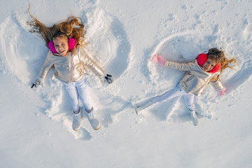 Two Girls on a snow angel shows. Smiling children lying on snow with copy space. Funny kids making snow angel. Top view.