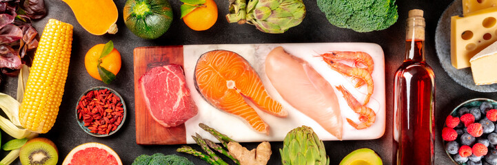 Food panorama, a flatlay with meat, fish, chicken and shrimps, vegetables and fruits, wine and cheese, shot from above on a dark background