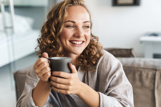 Cheerful young blonde haired woman drinking tea