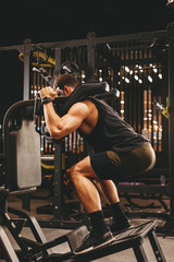 Athletic man doing legs exercise on squat machine at the gym