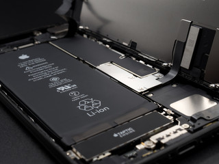 Chiangrai, Thailand: May 19, 2017 - Close-up image of Apple iPhone 7 jet black color disassembled for repair and showing components inside on black background. Selective focus.