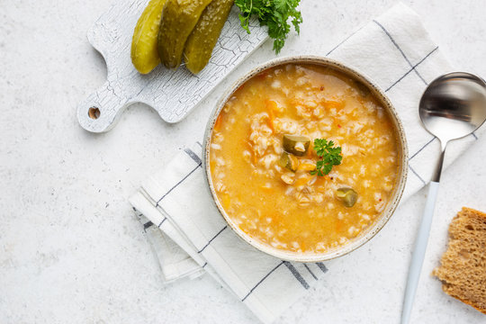 Soup with pickled cucumbers and pearl barley - rassolnik on white background, top view