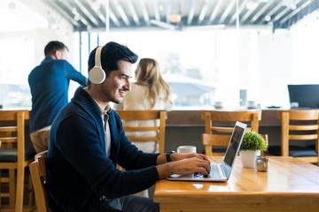 Male Freelancer Using Laptop At Restaurant