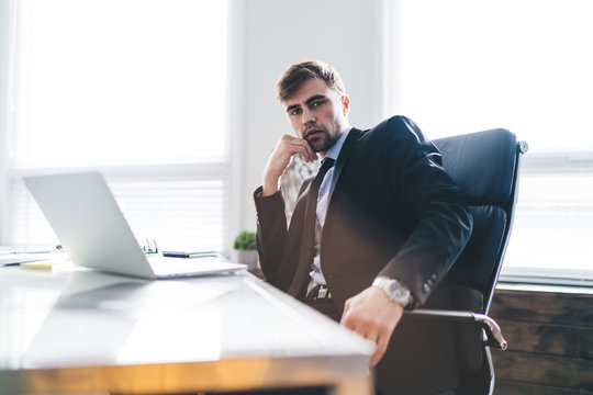 Handsome thoughtful businessman working in office
