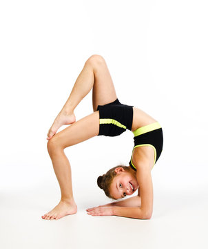 Flexible cute little girl child gymnast doing acrobatic exercise isolated on a white background