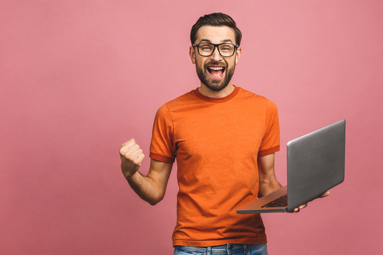 Image of happy excited young man posing isolated over pink background wall using laptop computer make winner gesture.