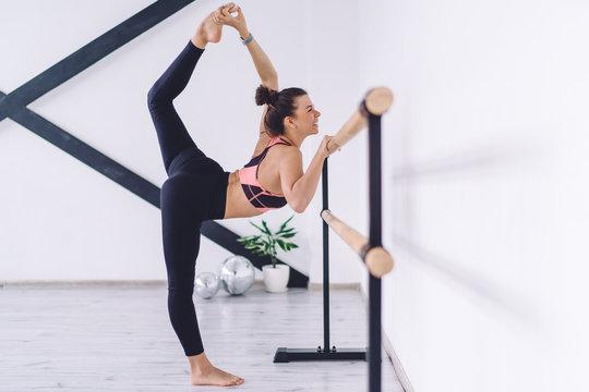 Cheerful ballerina practicing splits at barre